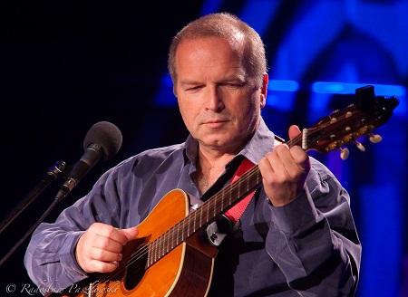 Mężczyzna w średnim wieku gra na gitarze.