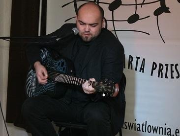 Na zdjęciu młody mężczyzna gra na gitarze klasycznej i śpiewa.