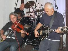 Na zdjęciu trzech mężczyzn na scenie, jeden gra na gitarze elektrycznej, drugi na altówce, trzeci na perkusji.