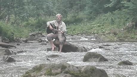 Mężczyzna z gitarą siedzi na kamieniu w górach.