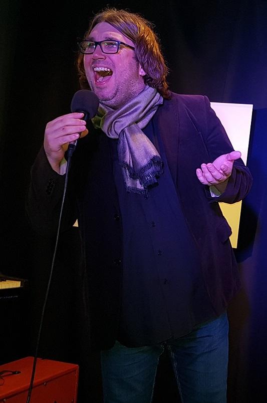 Na zdjęciu mężczyzna w okularach, włosy do ramion, otyły, śpiewa.