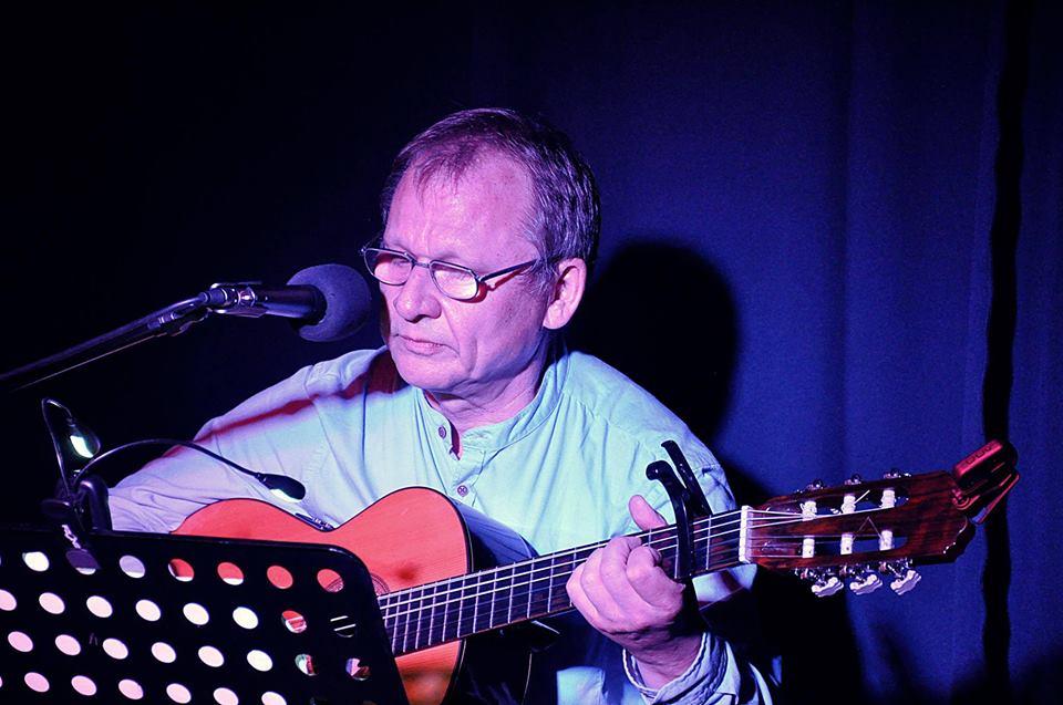 Mężczyzna w średnim wieku, w okularach, na scenie, gra na gitarze i śpiewa.