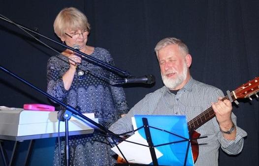 Kobieta śpiewa, mężczyzna gra na gitarze.