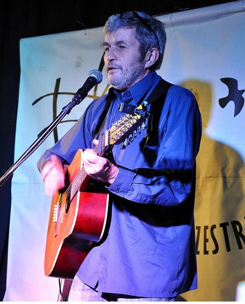 Na zdjęciu mężczyzna w średnim wieku, szczupły, w granatowej koszuli. Stoi na scenie i gra na gitarze akustycznej. W tle logo Światłowni.