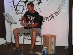 Na zdjęciu młody mężczyzna na scenie, gra na gitarze i śpiewa. Ubrany jest w krótkie spodenki, sandały.