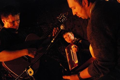 Na zdjęciu trzech młodych muzyków, dwóch gra na gitarze, jeden na akordeonie.