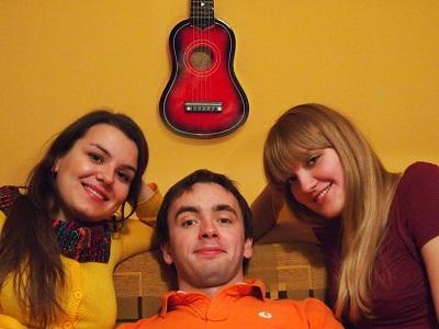 Na zdjęciu trzy młode uśmiechnięte osoby siedzące na kanapie, dwie dziewczyny i chłopak. Nad nimi na ścianie wisi czerwona gitara.