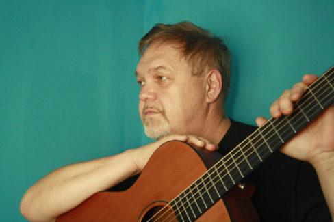 Mężczyzna w średnim wieku, z zarostem, opiera prawą rękę na gitarze. Patrzy w dal.