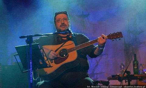 Na zdjęciu mężczyzna grający na gitarze.
