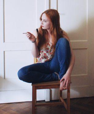 Młoda kobieta siedzi na krześle, w prawej ręce trzyma papierosa.