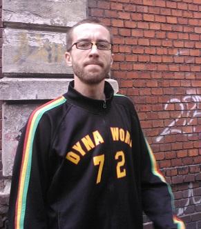 Na zdjęciu młody mężczyzna w okularach, w tle mur z czerwonej cegły.