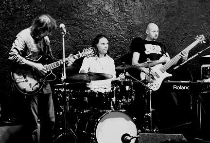 Trzech muzyków bluesowych na scenie.