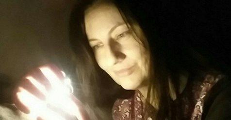 Na zdjęciu twarz młodej kobiety, patrzy na świetlną kulę