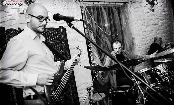 Dwóch panów w średnim wieku, w okularach, jeden gra na gitarze elektrycznej, drugi na perkusji.