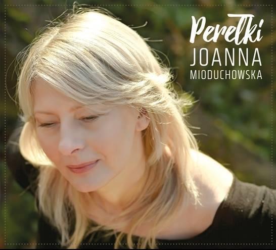 Blondyna w średnim wieku. U góry napis: Perełki. Joanna Mioduchowska