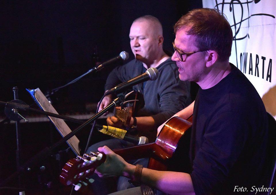 Dwóch mężczyzn w średnim wieku grają na gitarach i śpiewają