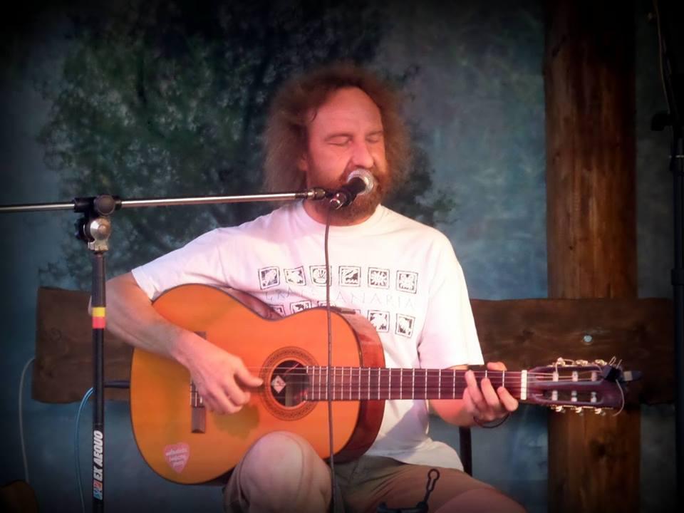 Mężczyzna gra na gitarze, włosy rozczochrane, brodaty.