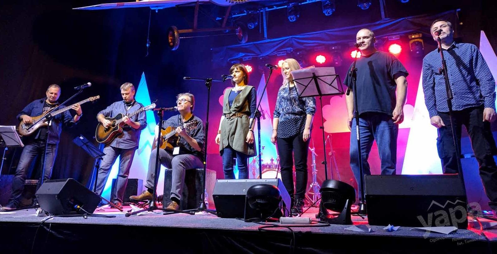 Zespół muzyczny stoi na scenie, 3 osoby graja na gitarach, 4 śpiewają