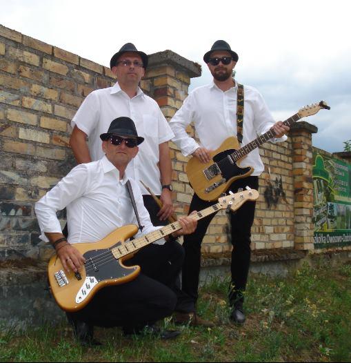 Trzech nężczyzn w białych koszulach, z gitarami pozuje do zdjęcia.