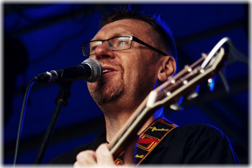 Mężczyzna w okularach, z gitarą, śpiewa