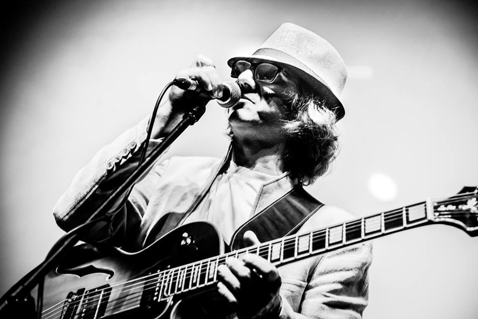 Mężczyzna w kapeluszu, gra na gitarze