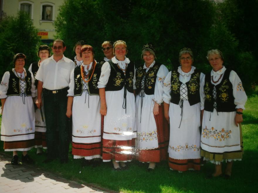 Dziewięć starszych kobiet w strojach ludowych i jeden mężczyzna w średnim wieku.