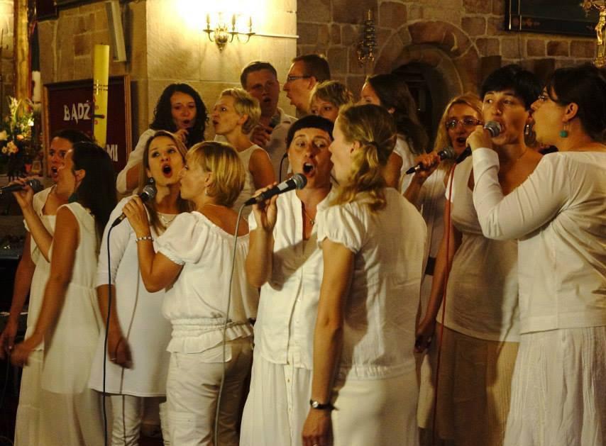 Grupa młodych ludzi ubranych na biało stoi na scenie, śpiewa
