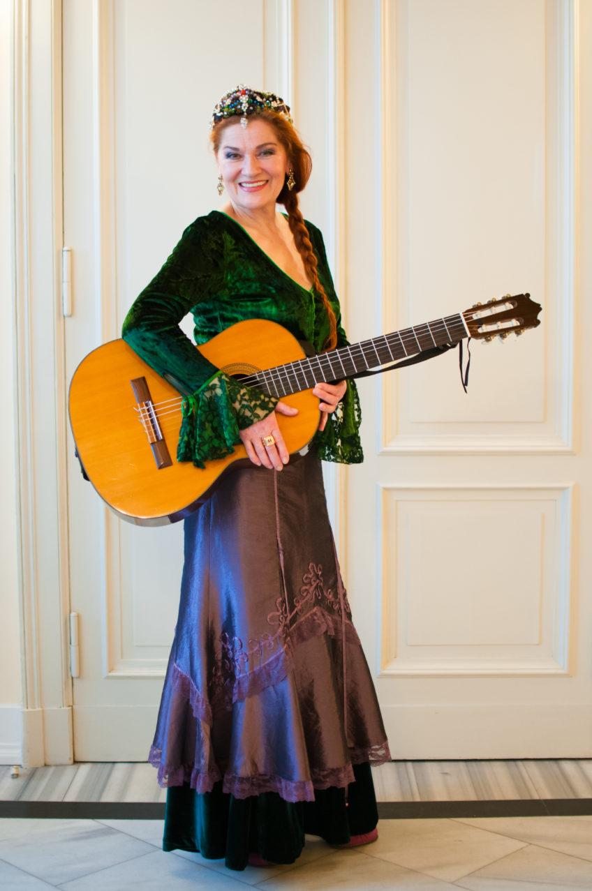 Kobieta w długiej sukni trzyma gitarę, uśmiecha się
