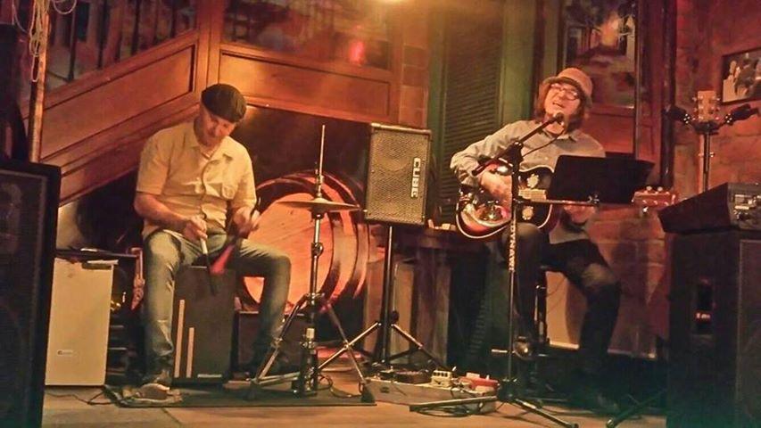 Dwóch muzyków na scenie: gitarzysta i perkusista