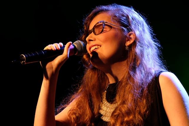 młoda kobitea w okularach śpiewa