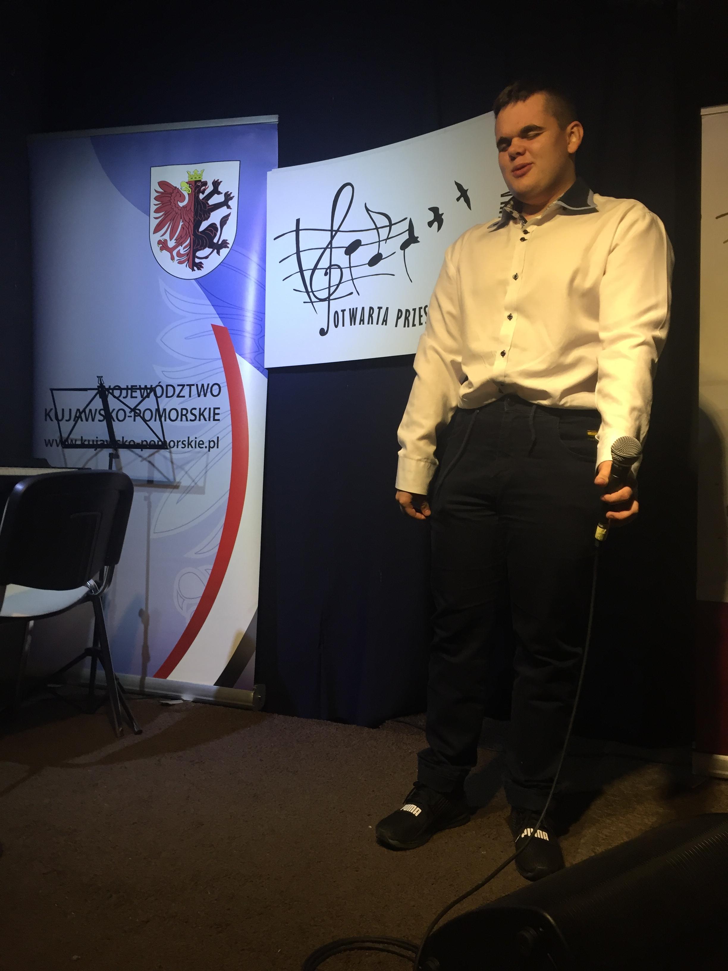Młody mężczyzna śpiewa na scenie