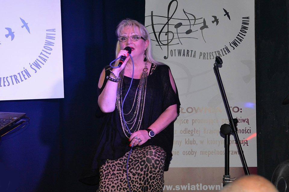 Kobieta w średnim wieku, w okularach, na scenie, śpiewa