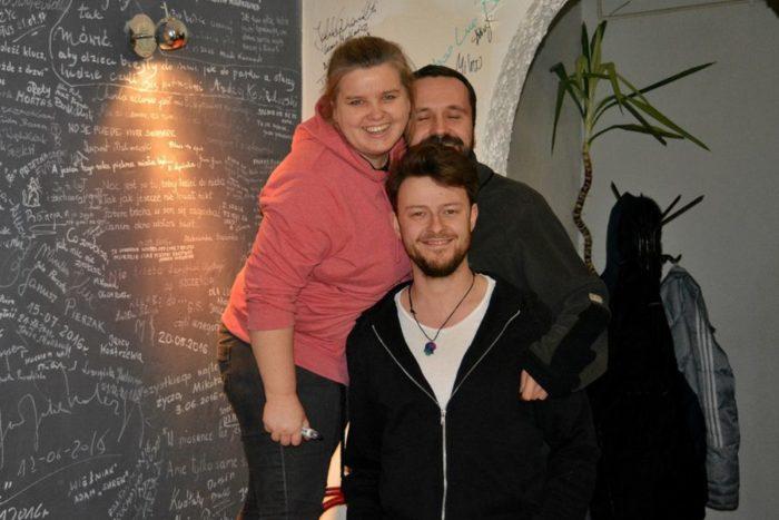 Młoda kobieta i dwóch młodych mężczyzn uśmiechają się