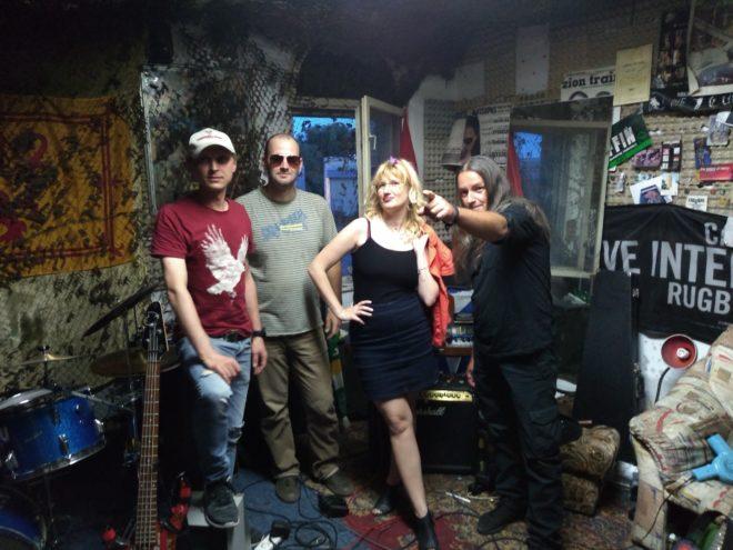 Trzech muzyków i kobieta w mrocznym pomieszczeniu