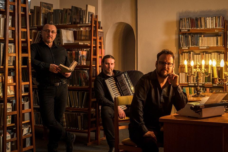 W bibliotecepozuje trzech młodych muzyków