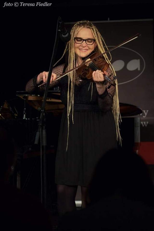 Kobieta w sukni do ziemi gra na skrzypcach i śpiewa