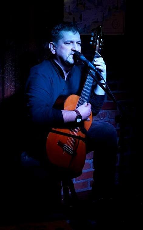 Mężczyzna w średnim wieku gra na gitarze i śpiewa