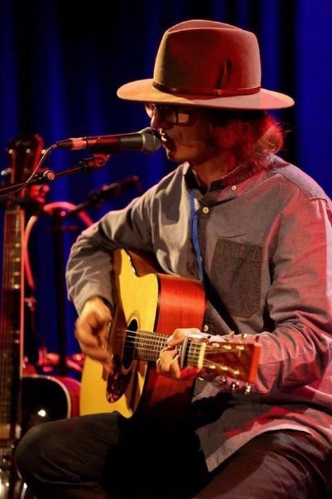 Mężczyzna w kapeluszu, gra na gitarze i śpiewa
