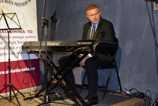 Mężczyzna w średnim wieku siedzi przy pianinie cyfrowym