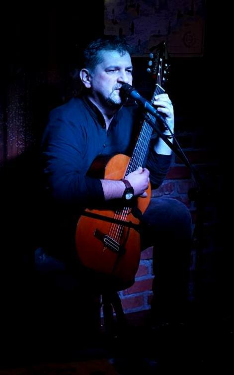 dojrzały mężczyzna gra na gitarze