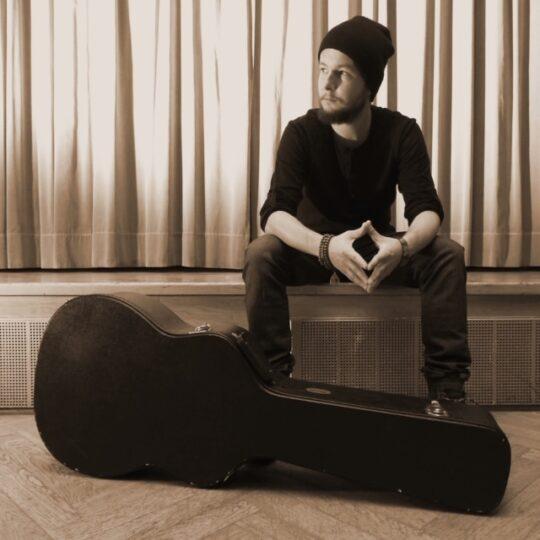 Młody mężczyzna w czapce, obok gitara