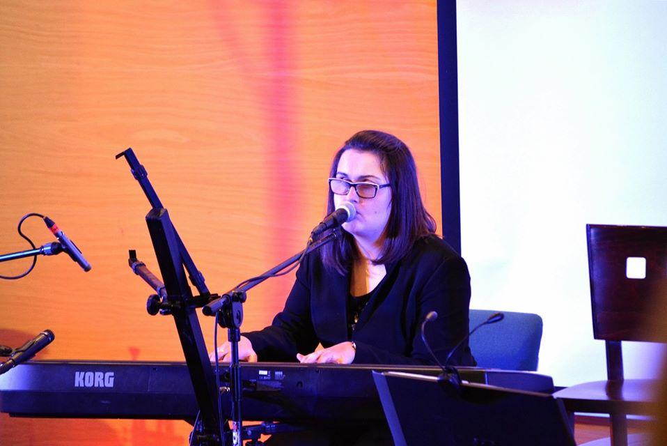 Młoda kobieta w okularach gra na pianinie