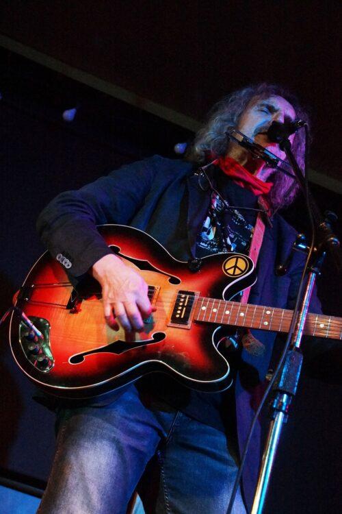 Długowłosy muzyk gra na gitarze
