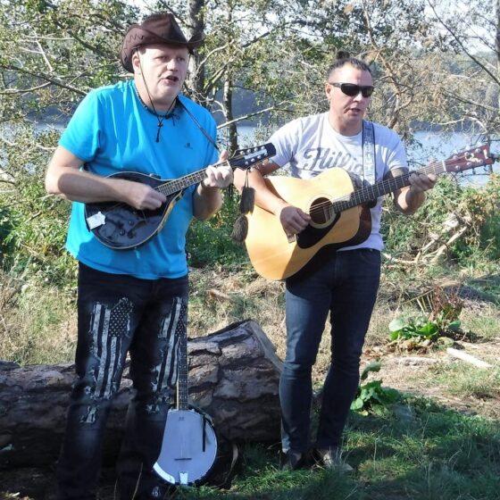dwóch mężczyzn w srednim wieku gra na gitarach
