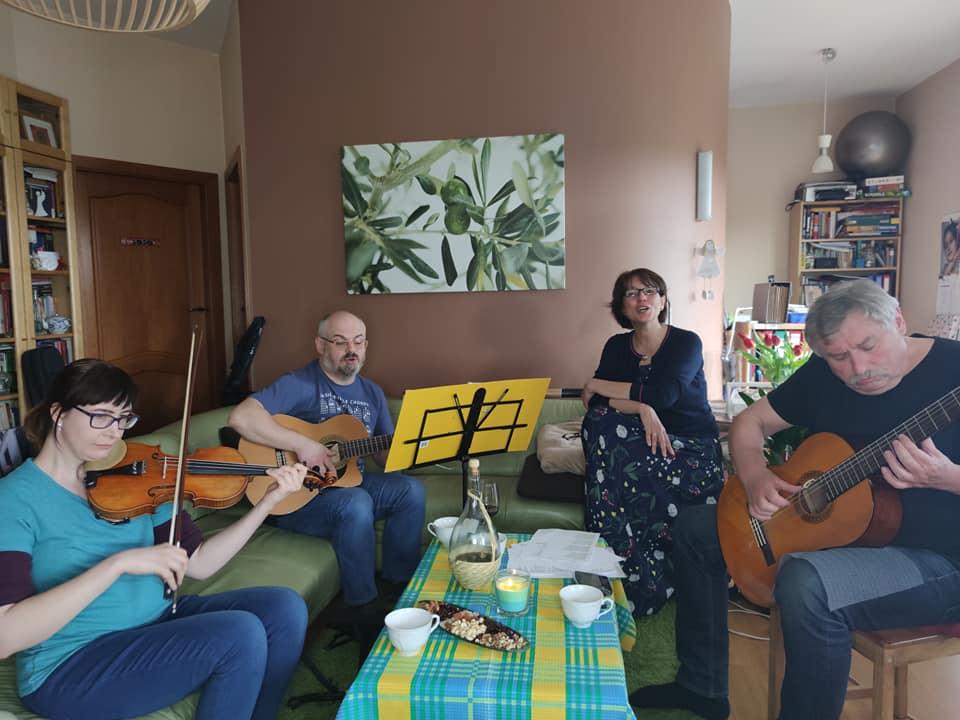 Dwóch gitarzystów , skrzypaczka i wokalistak siedzą na kanapach i muzykują