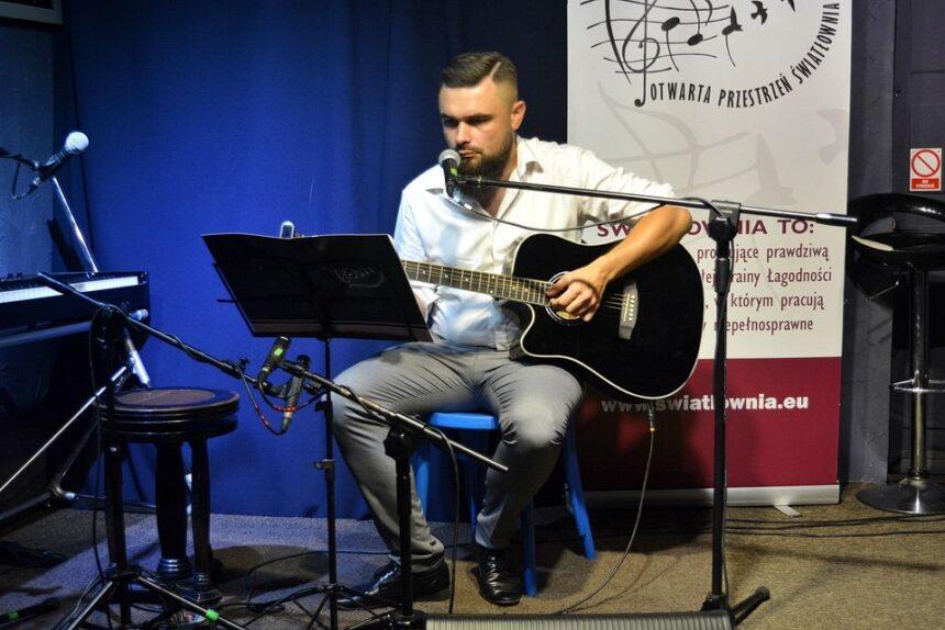 młody mężczyzna gra na gitarze na scenie