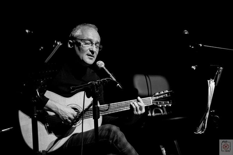 mężczyzna w średnim wieku gra na gitarze