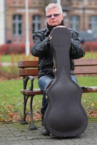mężczyzna w średnim wieku siedzi na ławce z gitarą