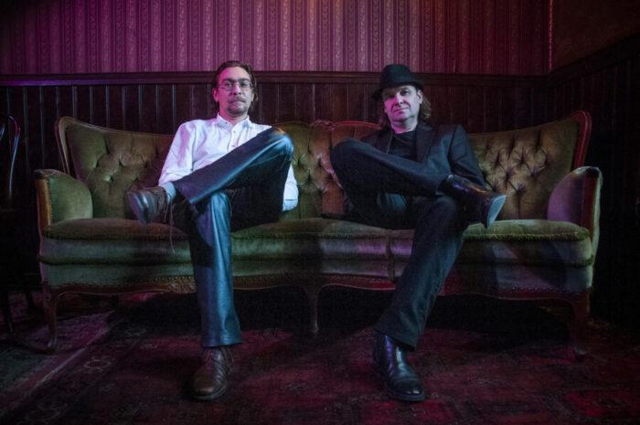 dwóch mężczyzn siedzi na kanapie