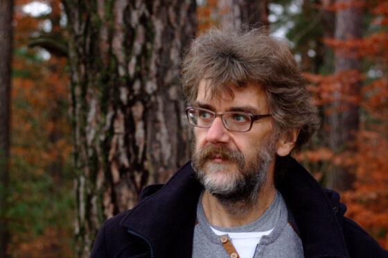 mężczyzna w okularach, z brodą patrzy w dal